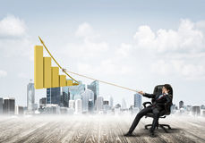 Man pulling with effort big pulling rope graph, as a symbol of financial growth Stock Photos