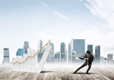 Man pulling with effort big pulling rope graph, as a symbol of financial growth Stock Photo