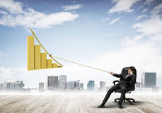 Man pulling with effort big pulling rope graph, as a symbol of financial growth Royalty Free Stock Images