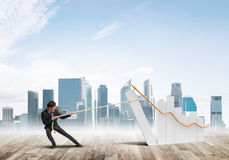Man pulling with effort big pulling rope graph, as a symbol of financial growth Royalty Free Stock Photos