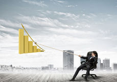 Man pulling with effort big pulling rope graph, as a symbol of financial growth Stock Photography