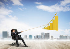 Man pulling with effort big pulling rope graph, as a symbol of financial growth Royalty Free Stock Image
