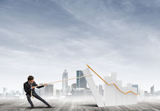 Man pulling with effort big pulling rope graph, as a symbol of financial growth Royalty Free Stock Photo