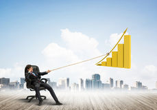 Man pulling with effort big pulling rope graph, as a symbol of financial growth. Young businessman outdoors making huge graph move Stock Photography