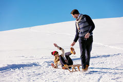 Man pulling girl on a sled at snow - concept: Winter fun Stock Photography