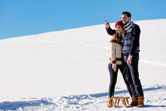 Man pulling girl on a sled at snow - concept: Winter fun Royalty Free Stock Photo