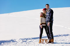 Man pulling girl on a sled at snow - concept: Winter fun Stock Photo