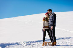 Man pulling girl on a sled at snow - concept: Winter fun Royalty Free Stock Image