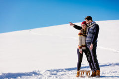 Man pulling girl on a sled at snow - concept: Winter fun Royalty Free Stock Photos