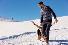 Man pulling girl on a sled at snow - concept: Winter fun Stock Image
