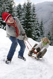 Man pulling girlfriend on sled on remote snowy hillside Royalty Free Stock Image