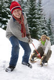 Man pulling girlfriend on sled on remote snowy hillside Royalty Free Stock Photography
