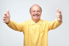 Man pulling hands towards camera and smiling friendly at camera wanting hug. Come into my arms. Handsome enthusiastic and caring european man with moustache stock images