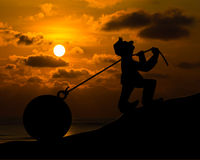 Man with pulling a heavy load ball silhouette Stock Photos