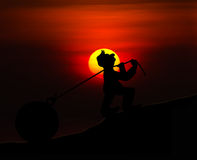 Man with pulling a heavy load ball silhouette with sunset Royalty Free Stock Images