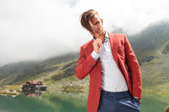 Man pulling his hair in front of a mountain lake Royalty Free Stock Photo