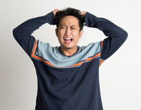 Man Pulling His Hair. Portrait Of Mad Asian Man Pulling His Hair On Plain Background Royalty Free Stock Photo
