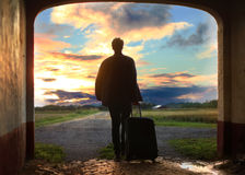 Man pulling luggage towards sunrise. Man pulling luggage away from home towards the afternoon sun Royalty Free Stock Images