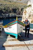 Man pulling a Maltese Dghajsa up a ramp at Blue Grotto. Man pulling a traditional Dghajsa water taxi up a ramp for mooring at the departure point with tourists Royalty Free Stock Photos