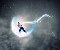 Man pulling moon. Young man in casual catching moon with rope Stock Photo