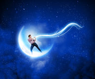 Man pulling moon. Young man in casual catching moon with rope Royalty Free Stock Photos