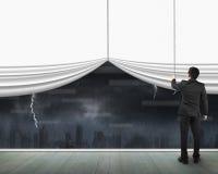 Man pulling open blank white curtain heavy rain dark cityscape Stock Photos