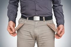 Man pulling out empty pockets - poor people concept. Young man pulling out empty pockets - poor people concept stock images