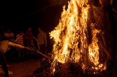 Man pulling out Prahlad effigy from holika dahan fire on hindu festival of holi stock photos