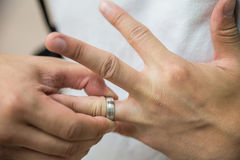 Man pulling ring off finger. Man pulling a wedding ring off from his finger Royalty Free Stock Photos