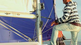 Man pulling rope, securing the mainsail on sailboat, yacht. Stock footage stock footage