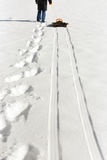 Man pulling a sledge in the deep snow, footprints and tracks Royalty Free Stock Images