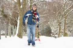 Man Pulling Sledge Through Winter Landscape Stock Images