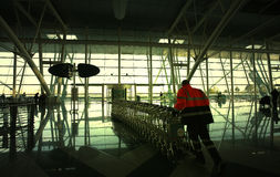 Man pulling trolleys. At the airport Stock Photos