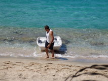 A man pulling up a dinghy at the beach. Stock Photos