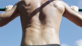 Man pulling up outdoors. The blue sky on the background. View from back stock footage