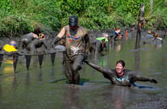 Man pulling woman through the mud Royalty Free Stock Photography