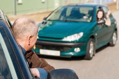 Man pulling a woman's car with problems Stock Photo