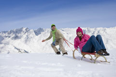 Man pulling woman up ski slope on sled Stock Image