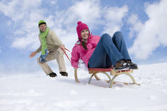Man pulling woman up ski slope on sled Royalty Free Stock Images