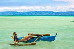 Philippines, Negros Island - Feb 05, 2018: Manjuyod White Sandbar. A man pulls the boat, walking on a spit during the surf stock photography