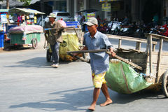 Man pulls a cart along the road, Thailand. Royalty Free Stock Photo