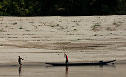 Man Pulls Fishing Boat on the Mekong River, Laos. A man pulls a fishing boat along the Mekong as the man in the boat pushes with a bamboo pole. The day is sunny Royalty Free Stock Photography