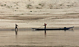 Man Pulls Fishing Boat on the Mekong River, Laos. A man pulls a fishing boat along the Mekong as the man in the boat pushes with a bamboo pole. The day is sunny Stock Photo