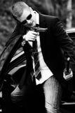 Man pulls a gun in car. Man pulls a gun in a mixed environment, like james bond Royalty Free Stock Image