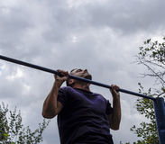 The man pulls himself up on the bar. Playing sports in the fresh air. Horizontal bar. Royalty Free Stock Photo