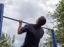 The man pulls himself up on the bar. Playing sports in the fresh air. Horizontal bar. Stock Photography