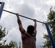 The man pulls himself up on the bar. Playing sports in the fresh air. Horizontal bar. Stock Photo