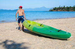 Man pulls a kayak to shore beach Stock Photo