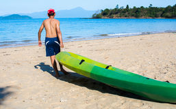 Man pulls a kayak to shore beach Royalty Free Stock Photo
