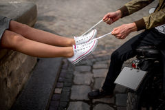 Man pulls the laces on the sneakers of his girlfriend sitting on the motorcycle Royalty Free Stock Photography